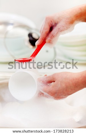 Woman hands washing dishes in the kitchen sink - closeup - stock photo
