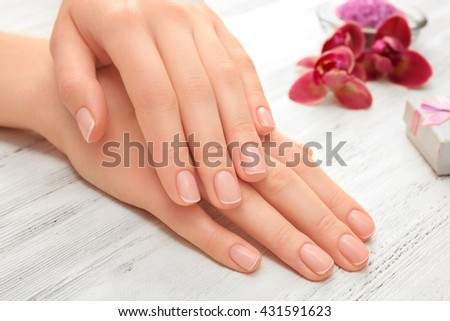 Woman hands with beautiful manicure and purple orchid on wooden background, close up - stock photo