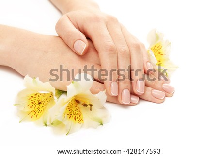 Woman hands with beautiful manicure and white lily isolated on white background - stock photo