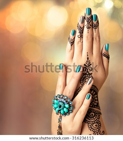 Woman Hands with black mehndi tattoo. Hands of Indian bride girl with black henna tattoos. Hand with perfect turquoise manicure and national Indian jewels. Fashion. India. Marriage traditions - stock photo