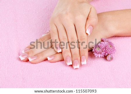 Woman hands with french manicure and flowers on pink towel - stock photo