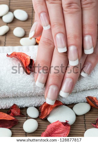 Woman hands with french manicure and flowers on wooden background - stock photo