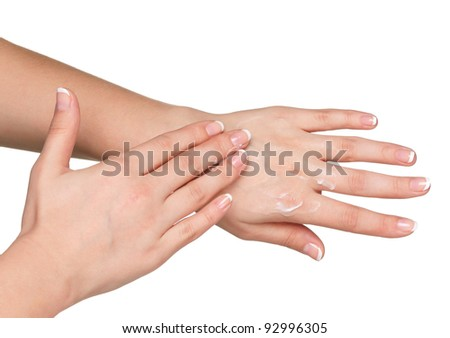Woman hands with french manicure applying hand cream isolated on white background - stock photo