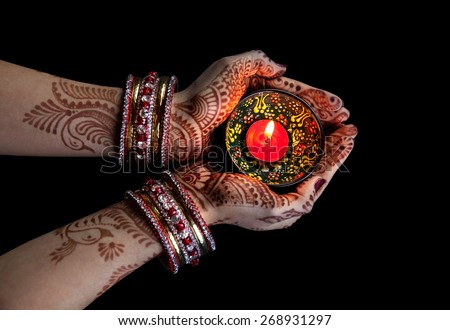 Woman hands with henna holding candle isolated on black background  - stock photo