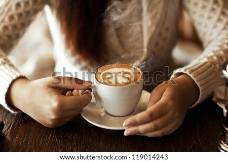 woman hands with latte on a wood table - stock photo