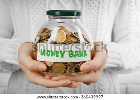 Woman hands with money in glass jar, close up - stock photo