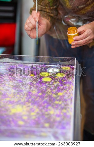 Woman hands with paintbrush marbling on water - stock photo