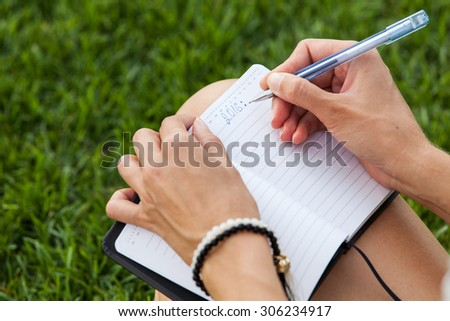 Woman hands with pen and notebook - stock photo