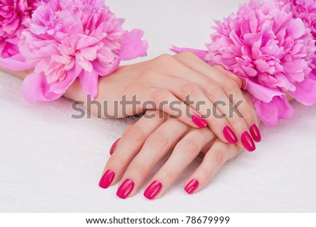 Woman hands with pink manicure lying down with flowers - stock photo