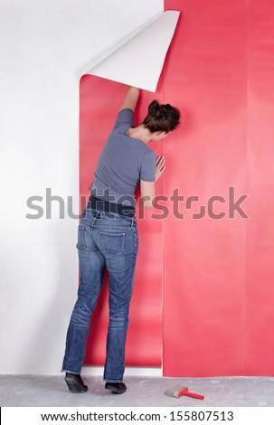Woman hanging wallpaper - stock photo