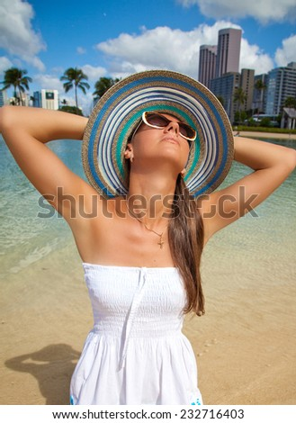 Woman happy and carefree on summer vacation in Waikiki most famous beach. Beautiful Girl Relaxing on Holiday - stock photo