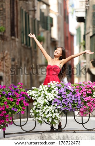 Woman happy in romantic Venice, Italy Girl standing in summer dress on bridge with flowers smiling joyful having fun. Beautiful multiracial Asian Caucasian young woman cheerful and vivacious. - stock photo