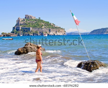 Woman has a walk along beautiful beach on Ischia island,Italy - stock photo