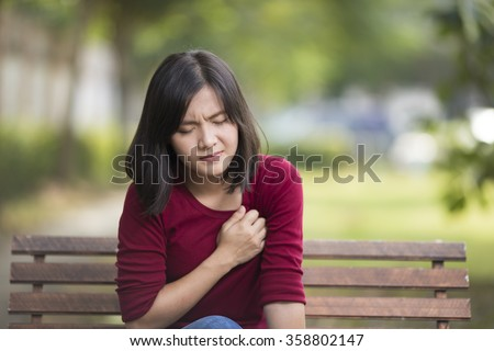 Woman Has Chest Pain Sitting on Bench at Park - stock photo