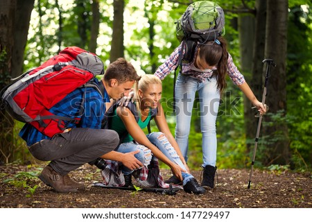 woman has sprained her ankle while hiking, her friends helps her  - stock photo