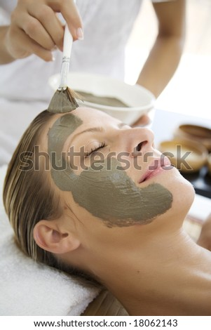 woman havin mud mask applied to her face by professional - stock photo