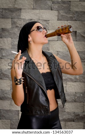Woman having a beer drink and a smoke. - stock photo