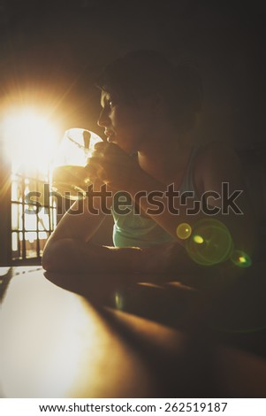 Woman having a cup of drink in a room with morning sun shining through the window - stock photo