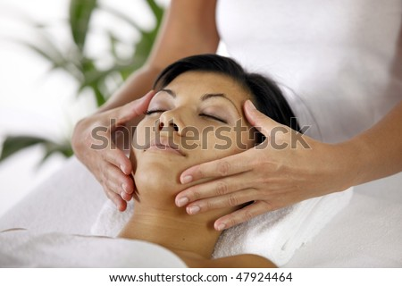 Woman having a face massage - stock photo