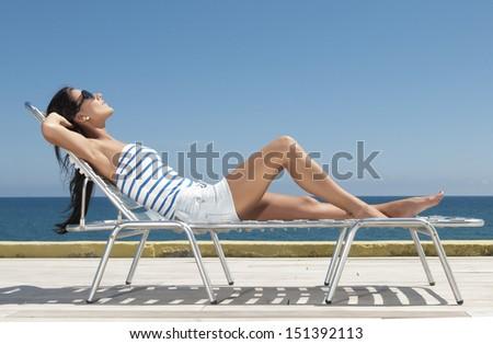 woman having a sun bath under the blue - stock photo