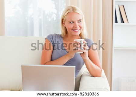Woman having a tea while holding a notebook in her living room - stock photo