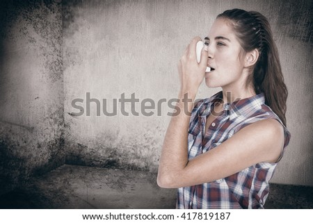Woman having asthma using the asthma inhaler against image of room corner - stock photo