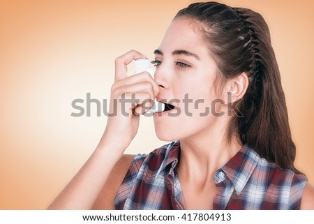 Woman having asthma using the asthma inhaler against orange vignette - stock photo