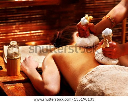 Woman having Ayurveda massage with herbal ball. - stock photo