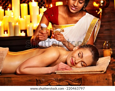Woman having ayurvedic massage with pouch of rice. - stock photo