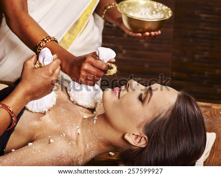 Woman having ayurvedic massage with pouch of rice. Close up. - stock photo