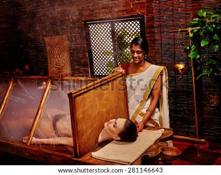 Woman having Ayurvedic sauna with steam treatment. - stock photo