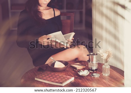 Woman having breakfast and reading book at home - stock photo