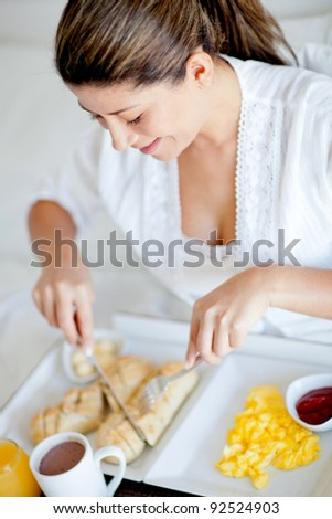 Woman having breakfast in the hotel room - stock photo
