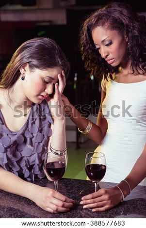 Woman having drinks and comforting her depressed friend in bar - stock photo