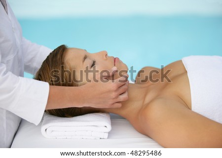 Woman having face massage by a swimming pool - stock photo