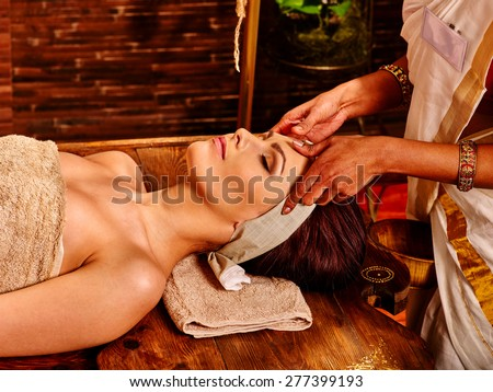 Woman having facial  ayurveda spa treatment. Wooden brown bed - stock photo