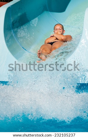 Woman having fun, sliding at water park. - stock photo