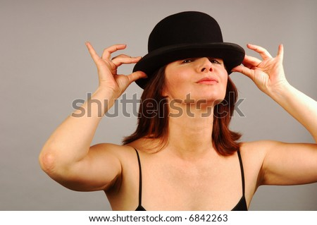 Woman having fun with a black bowler hat - stock photo