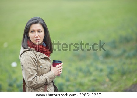 Woman having her morning coffee, with meadow blurred as background - stock photo