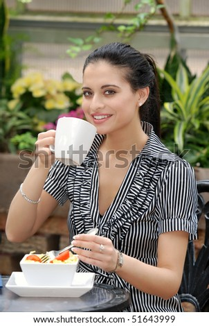 woman having lunch in outdoor cafe - stock photo