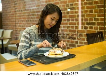 Woman having pancake at coffee shop - stock photo