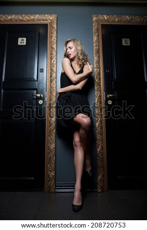 Woman having problems getting into toilet in the nightclub - stock photo