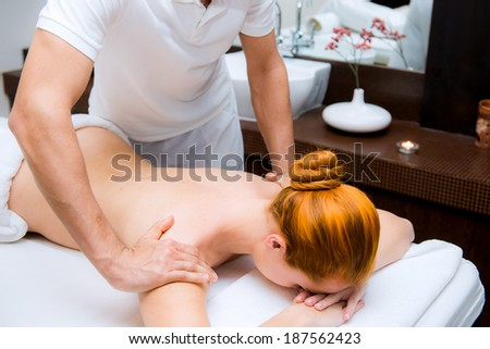 Woman having therapy massage of back in the spa salon.  - stock photo
