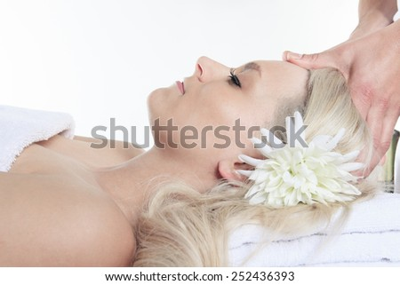 Woman having therapy massage of back in the spa salon. Beauty treatment concept. Blonde young woman relaxing with hand massage at beauty spa. Lumbar massage. Studio shot. White background. - stock photo