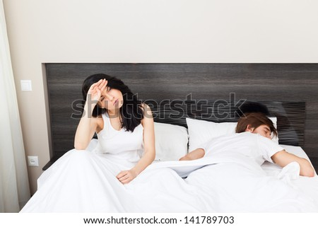 woman headache hold head pain, unhappy couple lying in a bed, having problem cheat separate, upset sad negative emotions concept - stock photo
