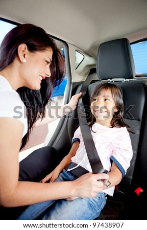 Woman helping a girl to fasten her seat belt in a car - stock photo