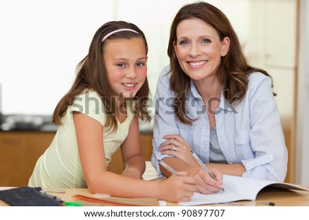 Woman helping her daughter with her homework - stock photo