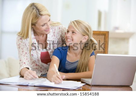 Woman helping young girl with laptop do homework in dining room smiling - stock photo