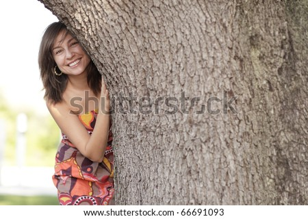 Woman hiding and smiling behind the tree - stock photo
