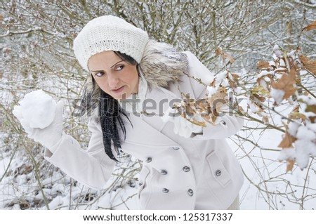 woman hiding behind tree about to throw snowball in snow covered forest - stock photo